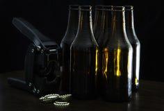 递有五个黑褐色瓶和盖帽的封盖罐头的人 免版税库存照片
