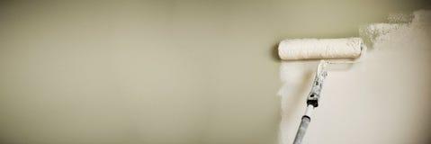 递有漆滚筒的,淡色绘画墙壁 公寓整修、修理、大厦和家庭概念 复制空间 免版税库存照片