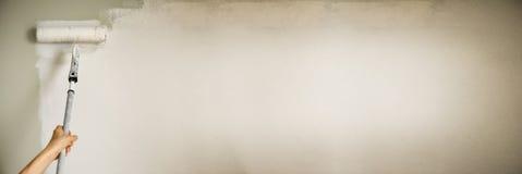 递有漆滚筒的,淡色绘画墙壁 公寓整修、修理、大厦和家庭概念 复制空间 图库摄影