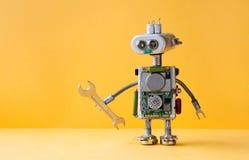 递板钳机器人黄色背景的军人工作者 靠机械装置维持生命的人玩具电灯泡注视顶头,电导线,电容器 免版税库存图片