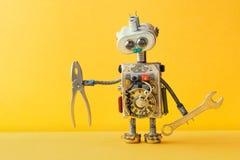 递板钳钳子黄色背景的机器人杂物工 靠机械装置维持生命的人玩具电灯泡注视顶头,电导线,电容器 库存图片