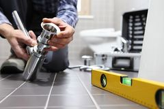 递水管工在工作在卫生间里,测量深度修理公司,  库存图片
