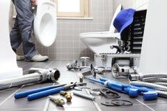 递水管工在工作在卫生间里,测量深度修理公司,  免版税库存照片