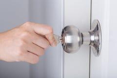 递用途打开的门把手钥匙在白色门 库存图片