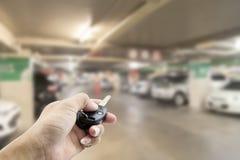 递男性亚洲,拿着汽车遥远在Blurred模糊的照片停车处  免版税库存图片
