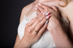 递白色婚礼礼服的美丽的女孩新娘与丙烯酸酯的钉子和精美样式和假钻石 免版税库存图片
