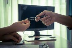 递笔的商人对合同签字的一名妇女 免版税库存照片