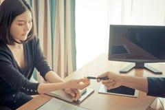 递笔的商人对合同签字的一名妇女 图库摄影