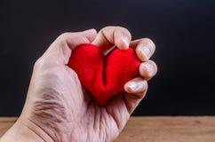 递紧压红色心脏,心脏病发作,爱问题概念 库存照片