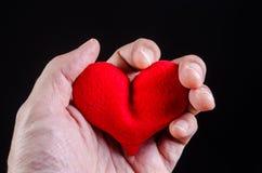 递紧压红色心脏,心脏病发作,爱问题概念 免版税库存照片