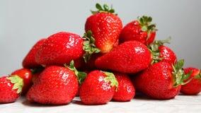 递采取在白色厨房背景的一个草莓 影视素材