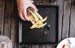 递采摘三明治前个片断,在方形的黑盘,在木桌上 免版税库存图片