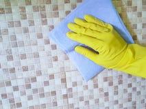 递黄色手套国内家庭与一块蓝色旧布玻璃的室内洗衣机房子窗口 库存照片
