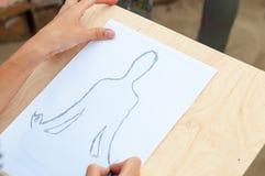 递画瑜伽凝思位置的一个人 库存照片