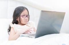逗人喜爱亚洲研究膝上型计算机坐床 库存图片