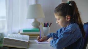 逗人喜爱做家庭作业的矮小的个学校女孩在桌上 股票录像