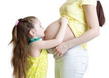 逗人喜爱儿童女孩拥抱怀孕的母亲腹部 免版税库存照片