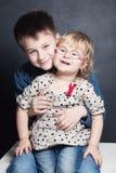 逗人喜爱儿童拥抱 背景兄弟查出的姐妹白色 库存照片