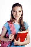 年轻逗人喜爱十几岁的女孩摆在快乐反对与书和背包的白色背景 免版税库存照片