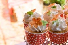逗人喜爱和五颜六色的美味的杯形蛋糕排 免版税库存图片