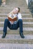 逗人喜爱和平静的白种人白肤金发的妇女阅读书画象,当走下去坐台阶户外时 免版税库存图片