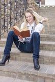 逗人喜爱和平静的白种人白肤金发的妇女阅读书画象,当走下去坐台阶户外时 库存照片