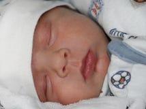逗人喜爱在白色和蓝色衣物的睡觉新出生的babywith天使面孔画象  平安地睡觉在床上的可爱的小孩 库存图片