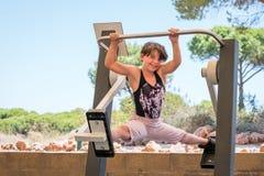 逗人喜爱女孩行使,做在发怒教练员健身房机器的分裂户外 库存图片