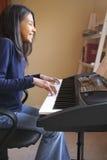 逗人喜爱女孩钢琴使用 库存图片