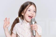 逗人喜爱小女孩唱歌 库存照片