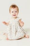 逗人喜爱小女孩微笑的坐皮 库存图片