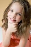 逗人喜爱小女孩微笑,倾斜在他的手肘 免版税图库摄影