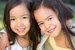 逗人喜爱小女孩拥抱 最好的朋友姐妹 免版税库存照片