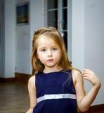 逗人喜爱小女孩摆在室内 免版税库存图片