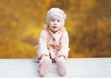 逗人喜爱小孩佩带被编织的衣裳在秋天 图库摄影
