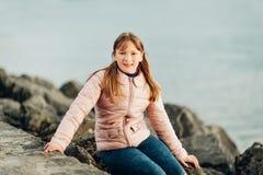 逗人喜爱小9-10使用由湖的岁女孩在一冷的天 免版税图库摄影