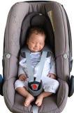 逗人喜爱新出生微笑在汽车座位 免版税库存图片