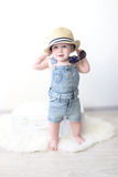 逗人喜爱时兴地穿戴10个月带着手提箱的女婴在ho 免版税图库摄影
