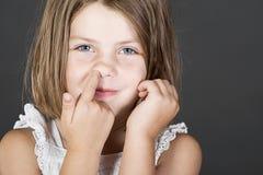 逗人喜爱白肤金发的子项她的鼻子挑&# 免版税库存图片