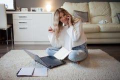 逗人喜爱白肤金发谈话在电话坐地板 与膝上型计算机一起使用,自由职业者的博客作者 免版税库存图片