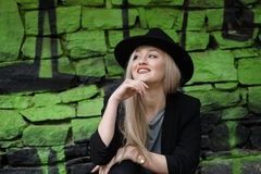 逗人喜爱白肤金发青少年对有绿色街道画的石墙 图库摄影