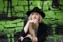 逗人喜爱白肤金发青少年对有绿色街道画的石墙 库存图片