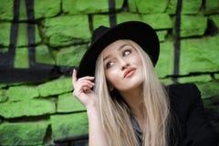 逗人喜爱白肤金发青少年对有绿色街道画的石墙 免版税图库摄影