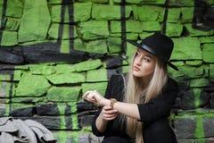 逗人喜爱白肤金发青少年对有绿色街道画的石墙 库存照片
