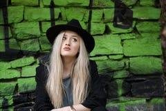逗人喜爱白肤金发青少年对有绿色街道画的石墙 免版税库存照片