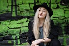 逗人喜爱白肤金发青少年对有绿色街道画的石墙 免版税库存图片