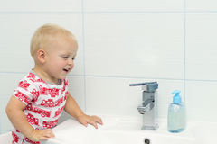逗人喜爱白色白种人男孩小孩一个岁洗涤的手特写镜头画象在卫生间和看起来里惊奇的激动, playin 免版税库存图片