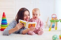 逗人喜爱的一起使用母亲和的女儿,读第一本书 免版税库存照片