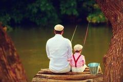 逗人喜爱的一起钓鱼在美好的原始自然中的父亲和儿子 免版税库存照片