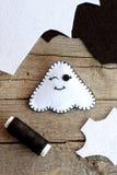 逗人喜爱的万圣夜鬼魂装饰,毛毡覆盖,在一张老木桌上的黑色螺纹 缝合的玩具 顶视图 免版税库存照片